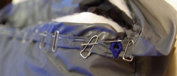 Oeillet et passage pour le cordon de serrage à la taille